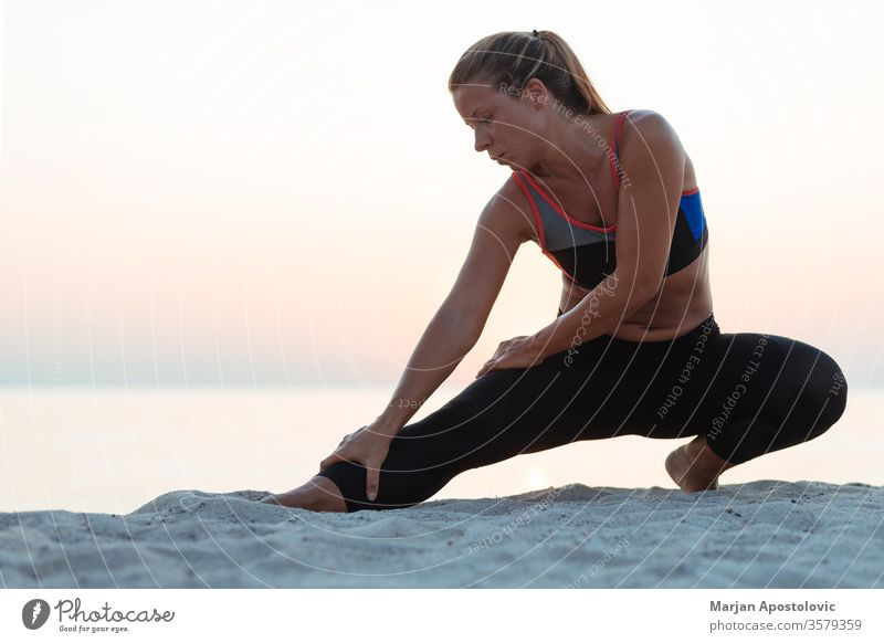 Junge sportliche Frau beim Stretching am Strand Sport strecken Läufer rennen Erholung Training Gesundheit passen jung Athlet Übung Lifestyle Fitness aktiv