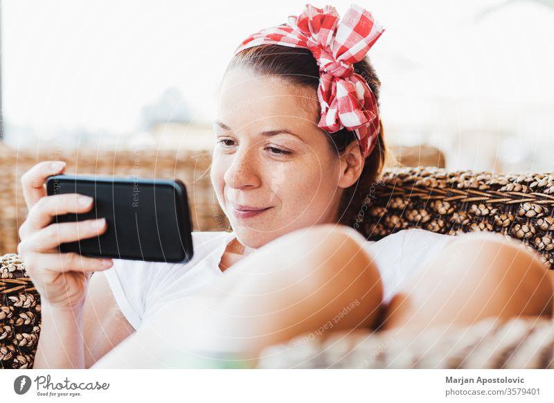 Junge Frau sieht Inhalte auf Smartphone jung Technik & Technologie Telefon WiFi Drahtlos Drahtlose Technologie benutzend Beteiligung Gerät Mädchen modern Sommer