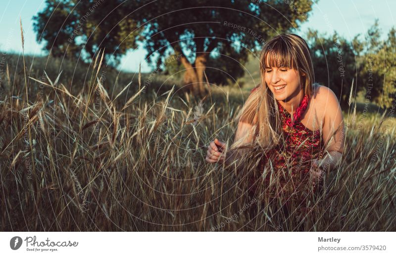 Hübsches junges blondes Modell, das bei Sonnenuntergang in einem Feld lächelt und ein Kleid trägt. Glückliche freie Frau in der Natur. Gemütliche Fotografie.