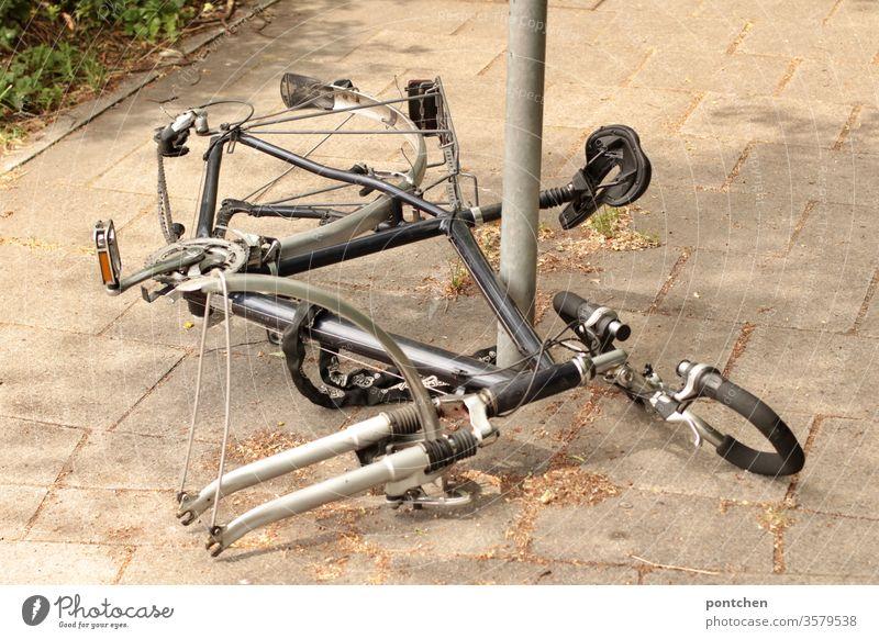 Überreste eines Fahrrades für Herren  an gekettet   an einen  Metallpfosten. Fahrraddiebstahl. Fahrradschloss. Sicherheit fahrradschloss fahrradteile