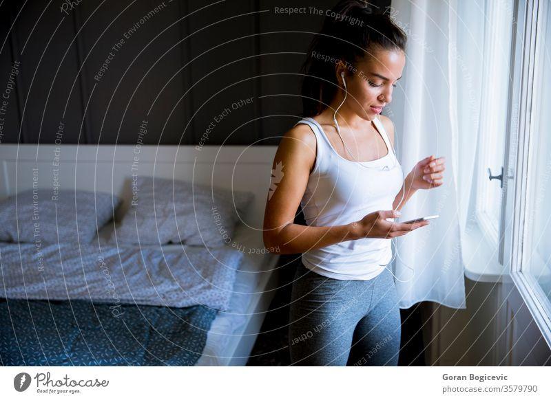 Junge, fitte Frau entscheidet sich für das richtige Grübeln bei den Übungen zu Hause jung passen Musik Fitness Athlet Sportbekleidung Mädchen Schlafzimmer
