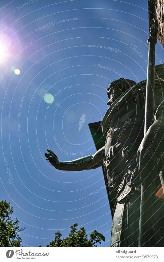 Ave ... Römer grüß mir die Sonne! Römische Statue vor dem Römerkastell Saalburg am Limes in Hessen hebt die Hand zum Gruß für Besucher und hält in der Hand einen Speer