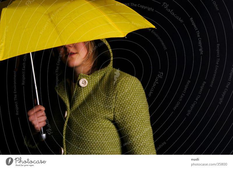 blickkontakt Frau gelb grün schwarz Kapuze Knöpfe Mantel Regenschirm Kopf verstecken Auge