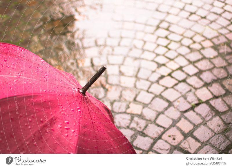 Regenschirm in pink und Naturstein - Pflaster, nass und glänzend magenta Schirm Pfütze Pflastersteine Natursteinpflaster Porphyr kalt Steinboden