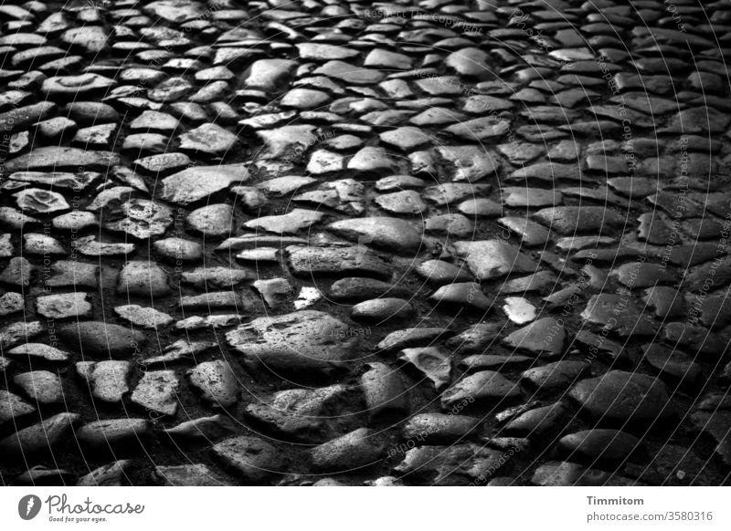 Alte Steine, alte Straße in alter Stadt Bodenbelag uneben glatt Licht Schatten Kontrast Schwarzweißfoto dunkel Wege & Pfade Menschenleer