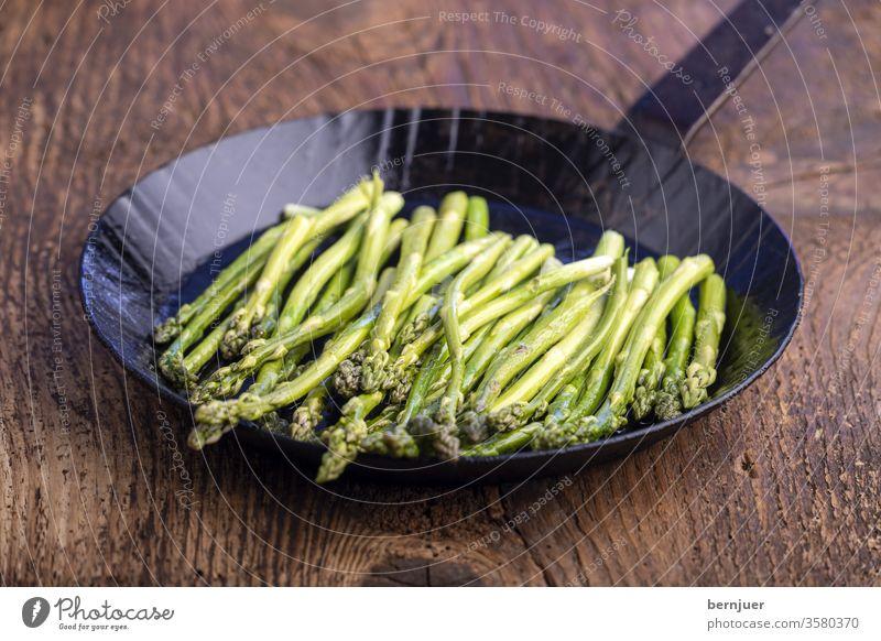 grüner Spargel in einer Eisenpfanne Kochen gesund Essen Grün Pfanne Küche frisch vegetarisch Vorbereitung Gemüse Zutat Mahlzeit schließen Hintergrund Ernährung