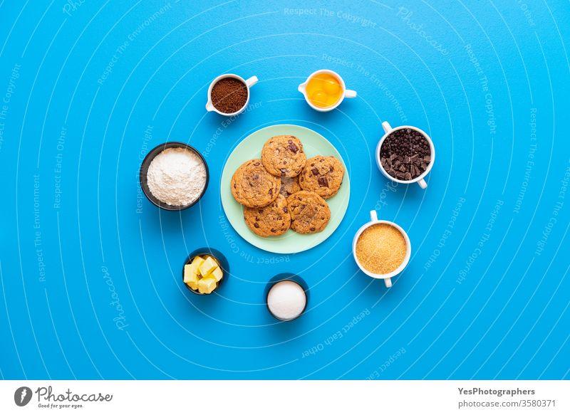 Schokokekse auf einem Teller und die Rezeptzutaten obere Ansicht Bäckerei backen Blauer Hintergrund Brauner Zucker Butter Schokoladenstückchen Schokoladenstücke