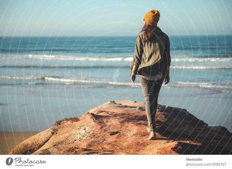 Schöne Frau am Strand Landschaft Spaziergang Rücken im Freien MEER Klippe Abenteuer reisen Reisender Ansicht Lifestyle Stil Urlaub Wanderung Seeküste wandern