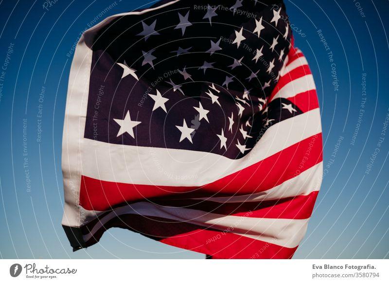 junge Frau, die bei Sonnenuntergang die Flagge der Vereinigten Staaten im Freien hält. Unabhängigkeitstag in Amerika, Konzept des 4. Juli Vereinigte Staaten