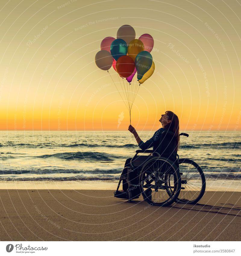 Alles ist möglich Frau Rollstuhl Glück Strand Ballons Sonnenuntergang Behinderte Gesundheitswesen Freude Freizeit Erfolg Motivation Aktivität Behinderung