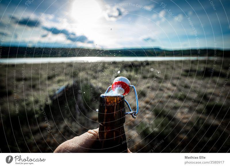 Genießt das Leben. Prost! Flasche Flaschenhals Bierflasche Bügelverschluss Büro Sonne Gegenlicht See Bierchen trinken Getränk Glasflasche Hand öffnen Biergarten