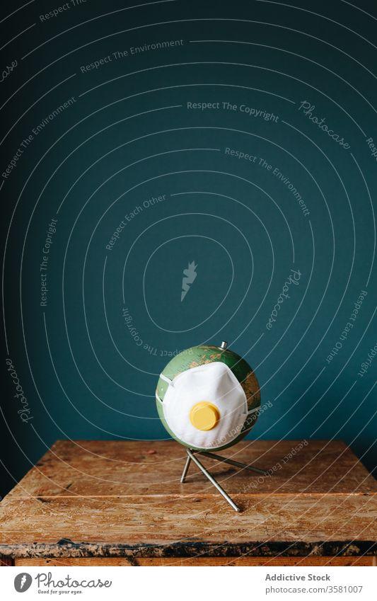 Kleiner Globus mit Atemschutzmaske auf dem Schreibtisch wenig Pandemie Atemschutzgerät Mundschutz Bund 19 COVID19 Coronavirus behüten Konzept kreativ Model