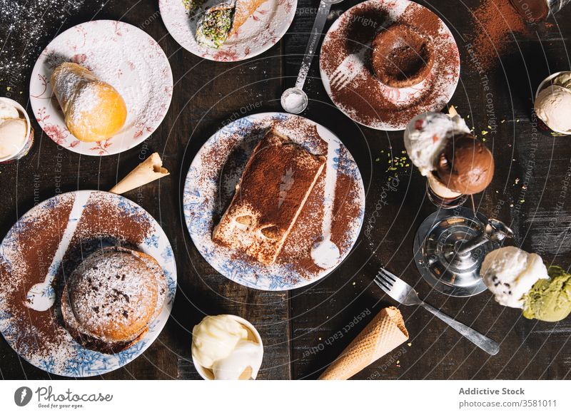 Set mit verschiedenen schmackhaften Desserts auf dem Tisch lecker süß Gebäck tiramisu Schokolade Kuchen Muffin Kulisse Kakao Zucker Pulver dienen Konditorei
