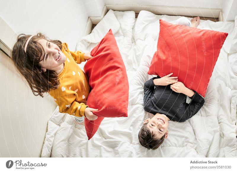 Verspielte Geschwister mit Kissenschlacht im Bett Geschwisterkind Kopfkissen kämpfen heimwärts Spaß Kinder Decke spielerisch spielen Bruder räkeln Schwester