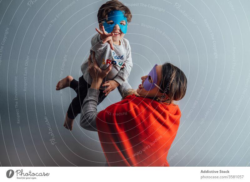 Lächelnde Mutter spielt mit Sohn zu Hause spielen Superheld werfen Mundschutz Spiel Spaß haben Junge Zusammensein so tun, als ob kreativ spielerisch heiter