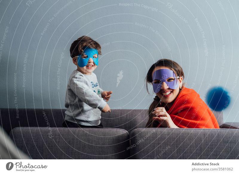 Kreative Mutter und Sohn in Superheldenmasken zu Hause spielen Mundschutz Spiel kreativ so tun, als ob Spaß haben spielerisch heiter wenig Wochenende Junge Kind