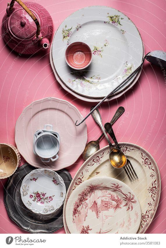 Satz bunter Keramikplatten und Glaswaren auf lebhaft rosa Oberfläche Teller Utensil Geschirr Besteck altehrwürdig Kulisse Küchengeräte Sammlung verschiedene