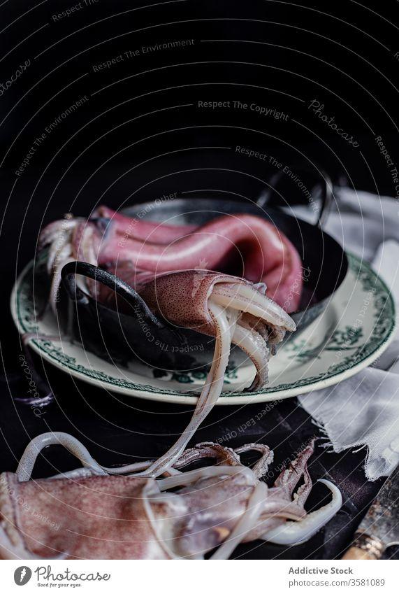 Rohe Tintenfische im Teller auf dem Tisch roh ungekocht Fleisch Küche altehrwürdig dunkel Schalen & Schüsseln Bestandteil Meeresfrüchte frisch Lebensmittel