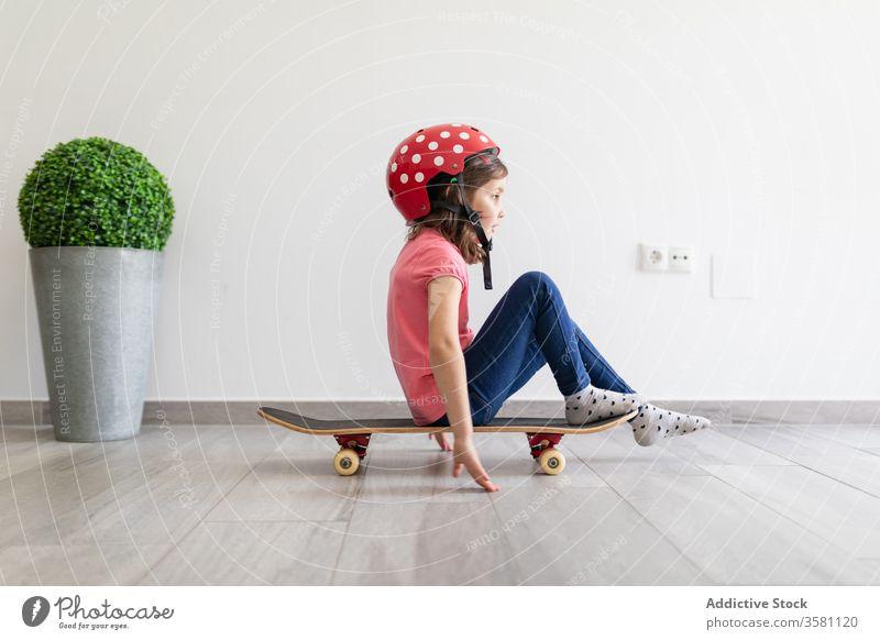 Glückliches Mädchen im Vorschulalter fährt zu Hause Skateboard heimwärts Spiel unterhalten Spaß Kind spielen Dekor Longboard Schutzhelm träumen zu Hause bleiben
