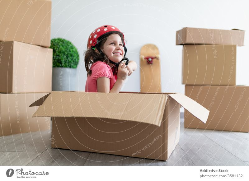 Fröhliches Mädchen spielt in Kartonschachtel spielen Kasten Lächeln Schutzhelm befestigen sitzen bewegend verlegen Spaß Vorstellungskraft Kind Phantasie Glück