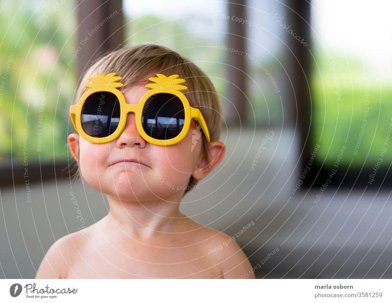 Kleiner Junge trägt eine Sonnenbrille mit gelber Ananas auf der hinteren Veranda Kleinkind mit Sonnenbrille Glück sonnig heimwärts Haus hintere Veranda