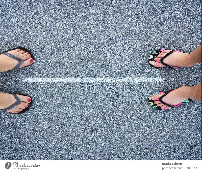 Blick von oben auf Erwachsener und Kind in Flip Flops mit einer Linie, die sie 6 Fuß voneinander trennt, soziales Distanzierungskonzept abgesehen Außenaufnahme