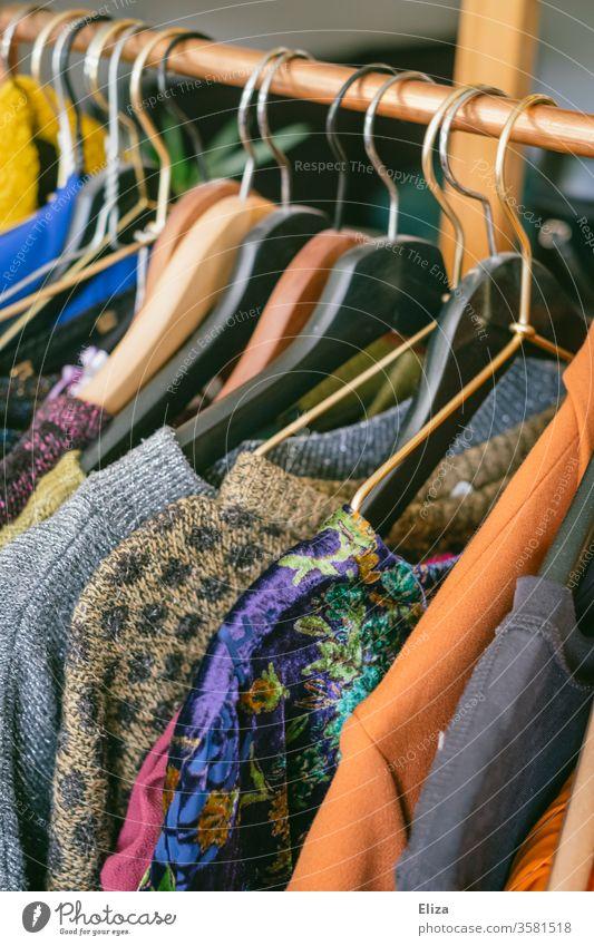 Kleidung auf einer Kleiderstange im Second Hand Geschäft oder auf dem Flohmarkt Second-Hand Laden gebraucht vintage Mode Bekleidung günstig slow fashion bunt