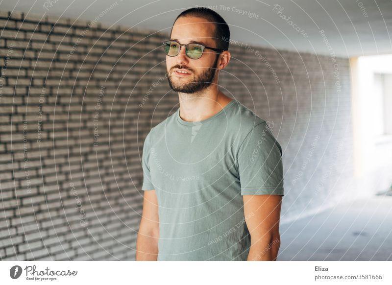Mann im T-Shirt steht in einer Unterführung und blickt nachdenklich in die Ferne. Vision. hell Visionär visionieren Wand Zukunft Brille gutaussehend braunhaarig