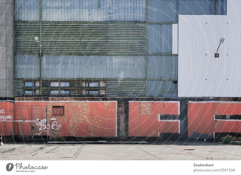 Fassade einer Fabrik aus Metall mit Rechteckmuster, darauf rotes Graffiti, in Oberschöneweide Rechtecke Lamellen grau weiß Laterne Grafitti urban Stadt
