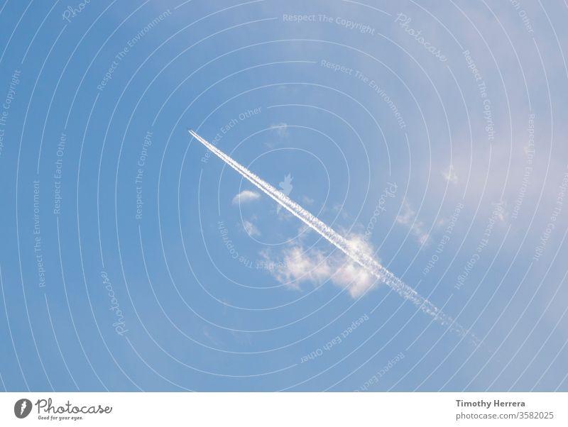 Ein Flugzeug, das einen Kondensstreifen oder Kondensstreifen hinterlässt. Himmel Blauer Himmel reisen Luftweg Wolken fliegen Urlaub Reise-Freizeit Freiheit