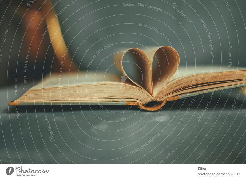 Ein aufgeschlagenes altes Buch dessen Seiten ein Herz bilden. Konzept Liebe zur Literatur und zum Lesen. Leidenschaft romantisch Roman Liebesromane