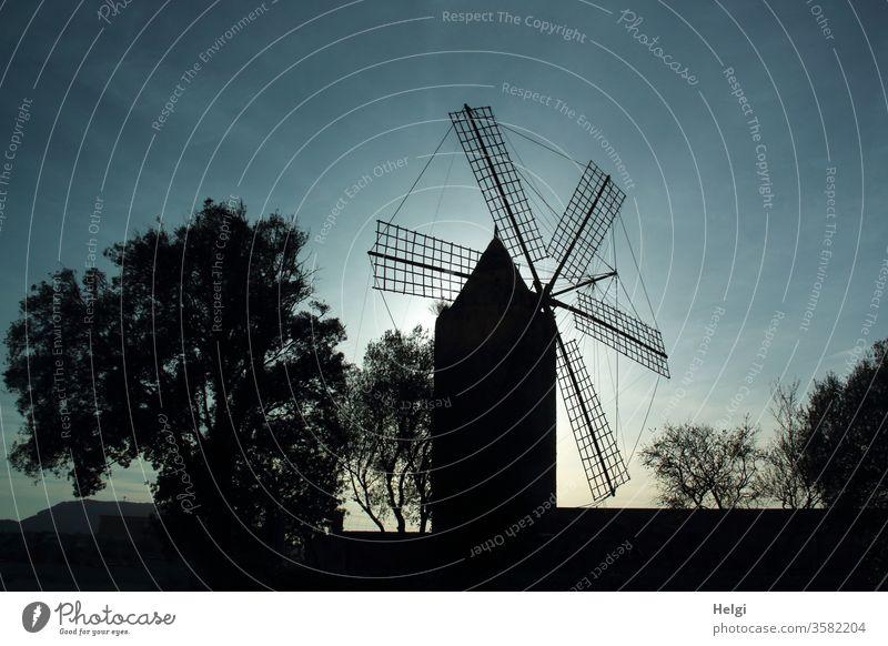 Silhouette einer Mühle zur Wassergewinnung auf Mallorca im Abendlicht Windmühle Himmel Licht Schatten Kontrast Baum Strauch Gegenlicht alt historisch Bauwerk
