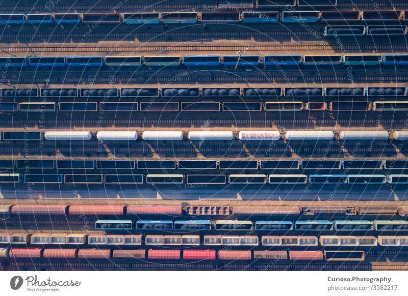 Luftaufnahme von bunten Güterzügen auf dem Bahnhof. Waggons mit Gütern auf der Bahn. Schwerindustrie. Industrielle Konzeptszene mit Zügen. Ansicht von oben. Mit Drohne aufgenommenes Foto.