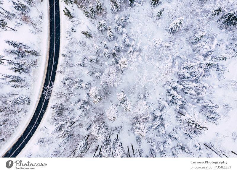 Kurvige, kurvenreiche, kurvenreiche Straße in schneebedecktem Wald, Luftaufnahme von oben. Winterlandschaft. Ansicht Antenne Top Dröhnen Schnee Landschaft Natur