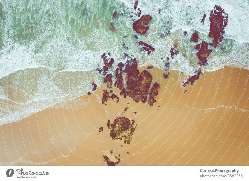 Luftaufnahme zu den Meereswellen. Gelber Sandstrand. Blauer Wasserhintergrund. Foto von oben von einer Drohne gemacht. Ansicht MEER Wellen Top winken Strand
