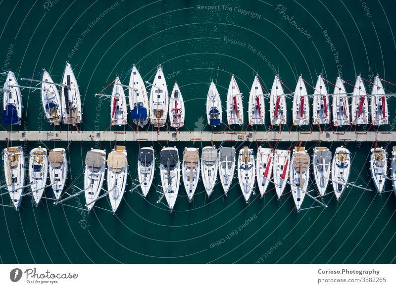 Luftaufnahme vieler weißer Boote und Yachten, die im Yachthafen liegen. Foto von Drohne von oben gemacht. Jachthafen Antenne Ansicht Pier MEER Dock Wasser