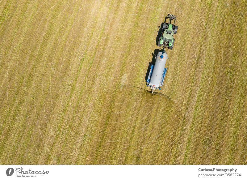 Luftaufnahme eines Ackerschleppers beim Pflügen und Spritzen auf dem Feld.  Landwirtschaft. Ansicht von oben. Mit Drohne aufgenommenes Foto. Antenne Maschine