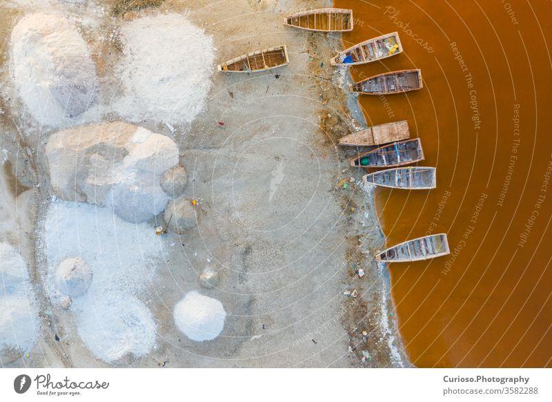 Luftaufnahme der kleinen Boote zum Salzsammeln am rosa Retba- oder Lac Rose-See im Senegal. Foto von Drohne von oben gemacht. Afrikanische Naturlandschaft.