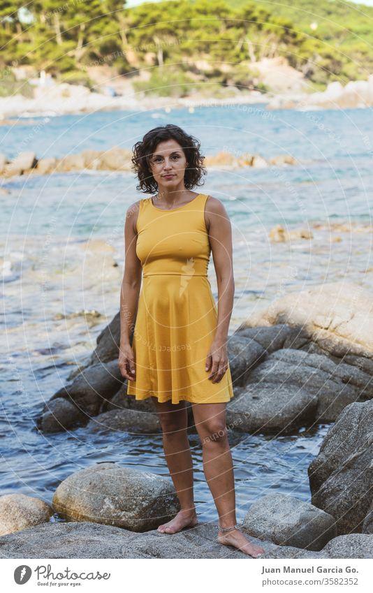 Eine schöne weibliche Latina in einem gelben Kleid steht auf einem Felsen am Meeresufer Frau Mädchen Schönheit jung hübsch attraktiv Menschen Erwachsener weiß