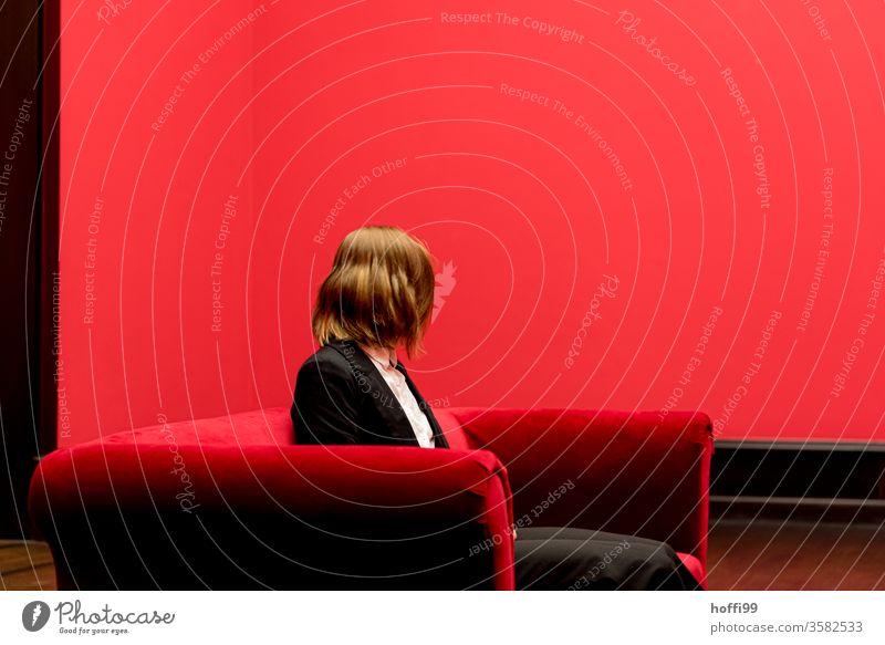 die junge Frau auf dem roten Sofa wendet sich ab - das Rot um sie rum ist ganz schön rot ... roter Raum Junge Frau Blick in die Kamera Drehung Schwung