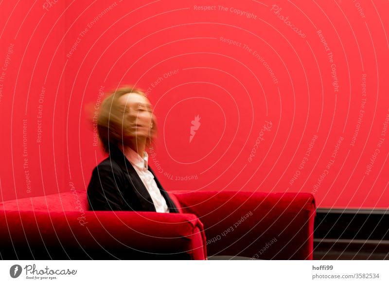 die junge Frau auf dem roten Sofa dreht sich sitzend und blickt in die Kamera - das Rot um sie rum ist ganz schön rot ... roter Raum Junge Frau