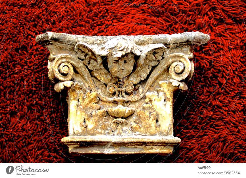 neoklassizistisches Fassadenelement mit verkniffener Putte - adrett präsentiert auf rotem Plüsch Neoklassizismus Skulptur historisch Bauteil Ornament