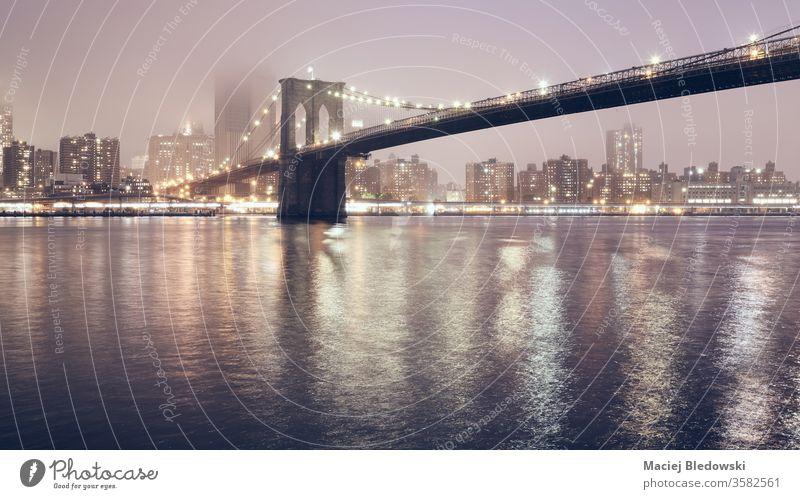 Brooklyn Bridge in einer nebligen Nacht, New York City, USA. New York State Großstadt Manhattan Skyline Nebel Wasser Reflexion & Spiegelung urban Himmel berühmt