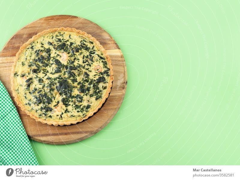 Gemüse-Quiche auf grünem Hintergrund. Leerzeichen kopieren. Spinat grüner Hintergrund Küchentisch Textfreiraum Draufsicht Lebensmittel Käse gebacken Mahlzeit