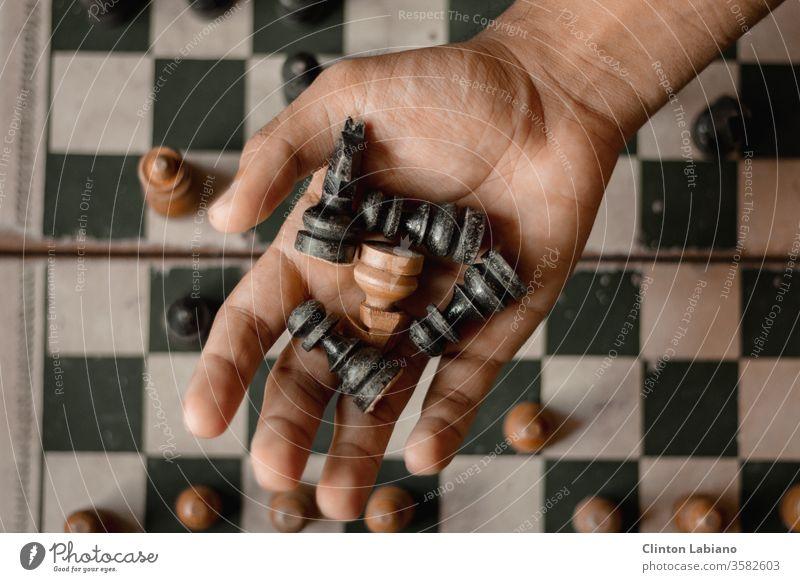 eine Hand, die fünf Schachfiguren hält schwarz weiß Schachbrett braun Spielzug packen Quadrat Holzmaserung klassisch Denksportaufgabe rustikal Holzbrett