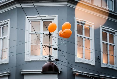 Eine Gruppe Luftballons hängen an einer Oberleitung fest Bewegung festhalten Fester Fassade Haus Hauswand Kreuzung Wand Menschenleer Gebäude Architektur Tag