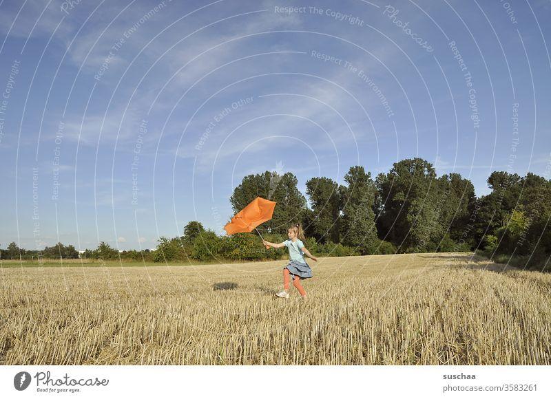 kind mit einem kaputten orangefarbenem regenschirm auf einem sommerlichen stoppelacker Kind Mädchen Sommer draußen schönes Wetter Natur Landschaft Stoppelacker