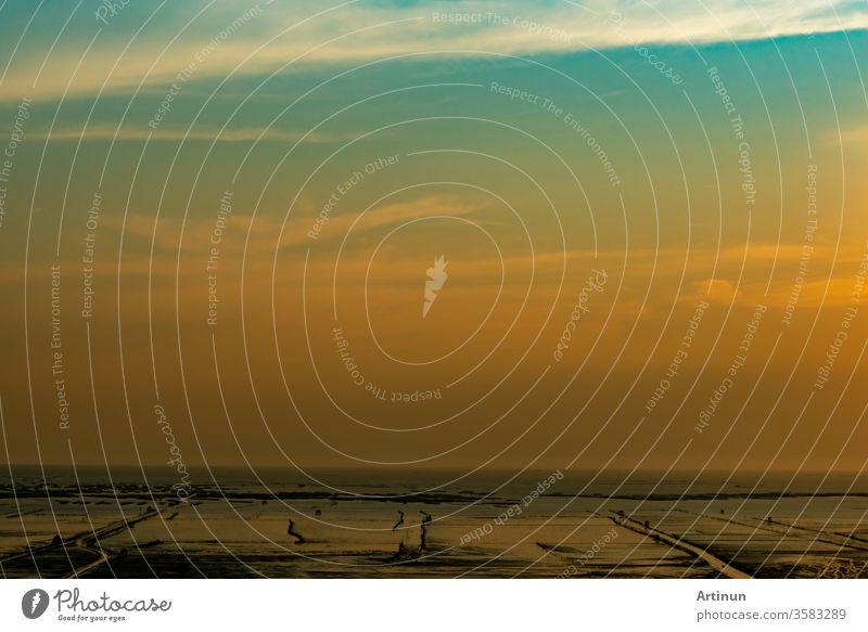 Orange und blauer Sonnenuntergangshimmel und Wolken. Sonnenuntergang am Strand. Schlammstrand am Meeresufer. Wunderschöne Skyline in der Abenddämmerung. Landschaft mit Schlammstrand und goldenem Himmel. Ruhiger und friedlicher Hintergrund. Liebe die Erde
