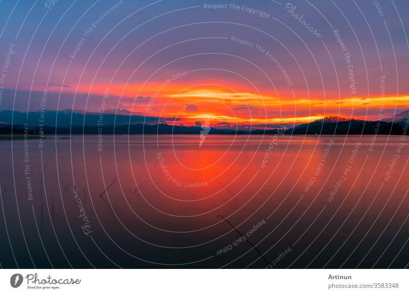 Roter und oranger Sonnenuntergangshimmel am Berg und am See. Wunderschöner Abendhimmel. Majestätischer Sonnenuntergangshimmel. Hintergrund der Natur. abstrakt