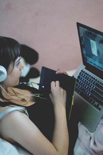 jugendliche mit kopfhörer sitzt im bett und zeichnet mit einem grafiktablett am laptop Jugendliche Teenager Jugendzimmer Bett Homeoffice Schülerin Schule